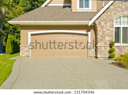 Double doors garage with wide and long driveway. North America.