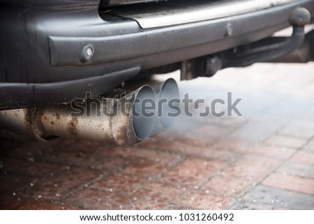 Double exhaust from an older car with diesel engine blows out gas with high particulate matter pollution, copy space, selected focus