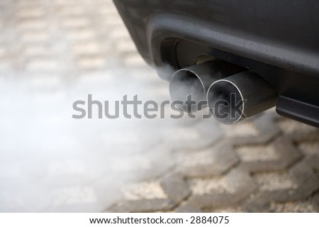 Double exhaust pipe of a car - blowing out the pollution.