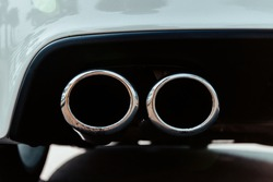 double exhaust pipe of a white sports car.