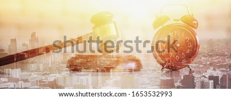 Double exposure-auction wood hammer and pink retro alarm clock, sunset cityscape background,auction control and business concept ストックフォト ©