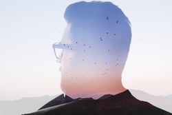 Double exposure back view portrait of a man combinated with beautiful landscape with birds and mountains on the sunset. Freedom and love of nature concept