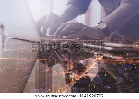 Double exposure business man working on laptop computer and cityscape at night, modern technology, smart business, internet of things IoT concept.