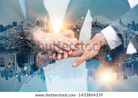 Double exposure Business people of Marketing team with a Partnership greeting power tag team,Teamwork Join Hands Partnership Concept after complete deal,Successful Teamwork Partnership in the city.