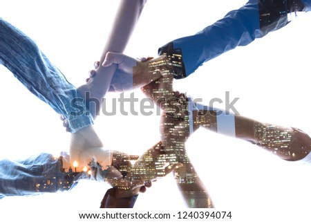 Double exposure Business  success Team which hand of the work force combine power tag team with light and Group of diversity people hand assembly high five together for good teamwork.
