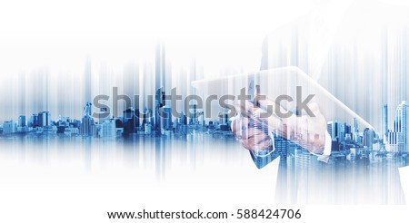 Double exposure businessman working on digital tablet with modern city, concepts of technology business development