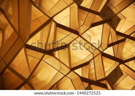Double exposure closeup photo of polygonal wooden wall panels. Abstract modern interior or architecture background in warm colors with cellular geometric structure.