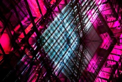 Double exposure colorized photo of transparent structural glazing of lift shaft. Colorful glass walls of an office building. Abstract modern architecture. Hi-tech construction with geometric structure