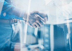 Double exposure concept.Close up view of business partnership handshake concept.Photo two businessman handshaking process.Skyscraper office building on the blurred background.Horizontal,flares