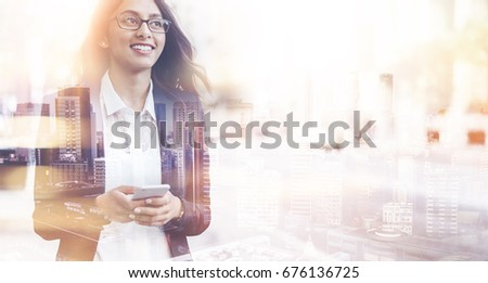 Double exposure concept smiling business woman wearing black suit and using modern smartphone near office during lunch time