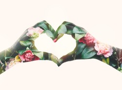 Double exposure effects on a silhouette of two hands in a shape of heart with garden flowers background. Conceptual image as a romantical symbol of love to nature and spring. Valentine's day holiday