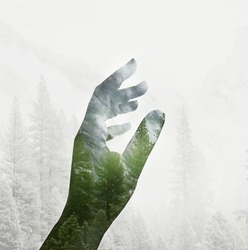 Double exposure effects on silhouette hand combined with photograph of green forest mountains landscape. Conceptual, abstract. Nature, ecology, environment, earth. Save the planet green
