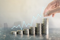 Double exposure hand stacking coins on blur background of city with profit line chart growth up. Business, finance, marketing, e-commerce concept and design