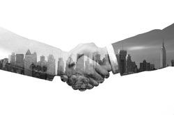double exposure handshake between businessman on a city background