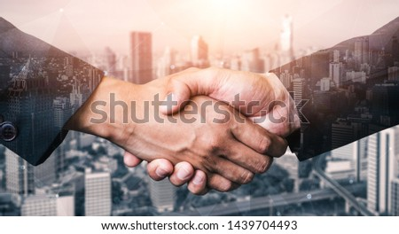 Double exposure image of business people handshake on city office building in background showing partnership success of business deal. Concept of corporate teamwork, trust partner and work agreement. #1439704493