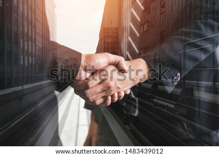 Double exposure image of business people handshake on city office building in background showing partnership success of business deal. Concept of corporate teamwork, trust partner and work agreement. #1483439012