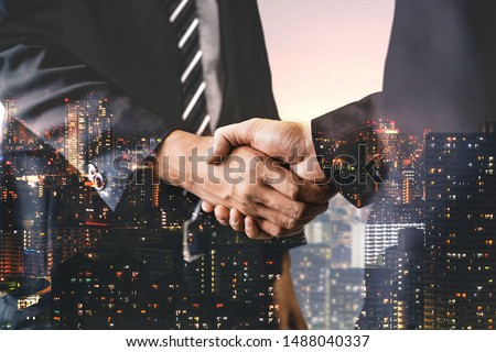 Double exposure image of business people handshake on city office building in background showing partnership success of business deal. Concept of corporate teamwork, trust partner and work agreement. #1488040337