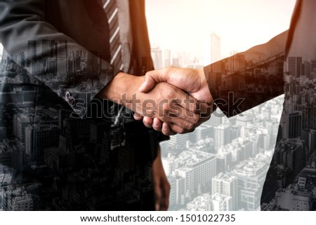 Double exposure image of business people handshake on city office building in background showing partnership success of business deal. Concept of corporate teamwork, trust partner and work agreement. #1501022735