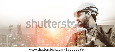 Double exposure image of construction worker with tablet computer and wearing construction uniform against the background of surreal construction site in the city.