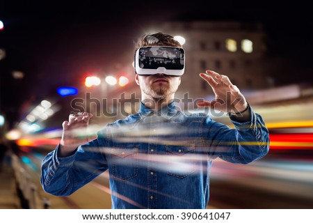 Double exposure, man wearing virtual reality goggles, night city