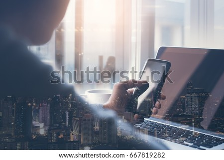 Double exposure man working on laptop computer using smart phone and smart city, internet application on phone and computer devices, start up business, software development, internet of things concept