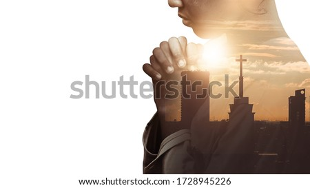 Double exposure of a hand girl praying for city, Hands folded in prayer concept for faith, spirituality and religion, Church in the city with sky background.
