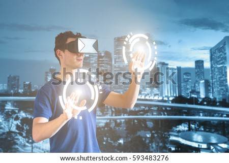 Double exposure of a person wearing virtual reality (VR) headset or glasses and touching buttons with a modern cityscape