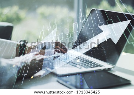 Double exposure of abstract creative financial diagram with upward arrow and hands typing on computer keyboard on background, growth and development concept Foto stock ©
