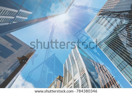 Double exposure of abstract real estate construction site and modern business skyscrapers, high-rise architecture buildings raising to the sky. Concepts of business financial, economics. #784380346