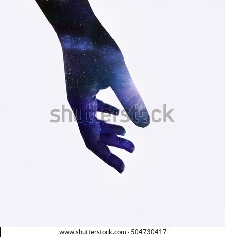 Double exposure of black painted hand combined with overlay texture of colorful space sky image full of stars. Conceptual, abstract, spiritual. Isolated on gray
