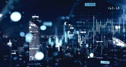 Double exposure of blurry financial graphs over night cityscape background. Concept of trading. Toned image