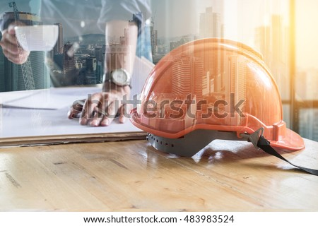 Double exposure of Building constructure and Image of engineer holding a cup of coffee and check blue print. selective focus