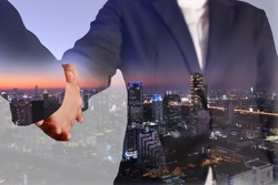 Double exposure of business handshake and night city as commitment, economy, partnership and investment concept.