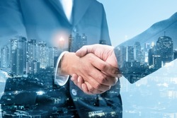 Double exposure of business handshake for successful of investment deal and city night background, teamwork and partnership concept, blue tone.