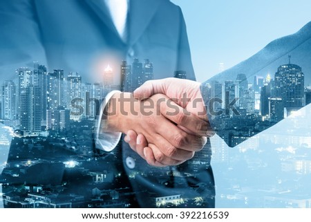 Double exposure of business handshake for successful of investment deal and city night background, teamwork and partnership concept, blue tone. - Shutterstock ID 392216539