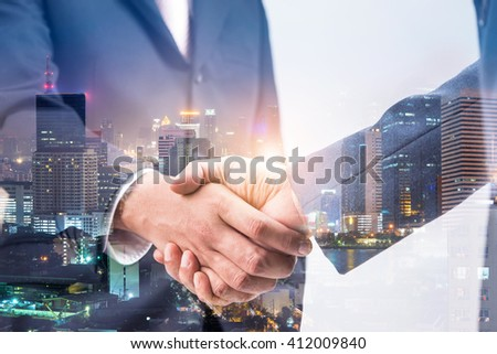 Double exposure of business handshake for successful of investment deal and city night background, teamwork and partnership concept.  - Shutterstock ID 412009840