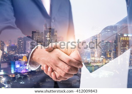 Double exposure of business handshake for successful of investment deal and city night background, teamwork and partnership concept.  - Shutterstock ID 412009843