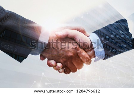 double exposure of business man handshake on modern office building background with network connection graphic diagram, partnership business,  teamwork global, technology and digital internet concept