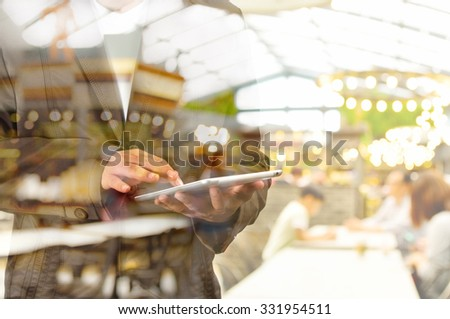 Double Exposure of Business Man using Mobile Tablet PC with Restaurant and Bokeh #331954511