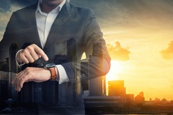 Double exposure of Businessman checking time on his watch , Businessman watching time at their wristwatches on a city during sunset time , Business. Punctuality and People Concept