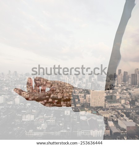 Double exposure of businessman hand and city background