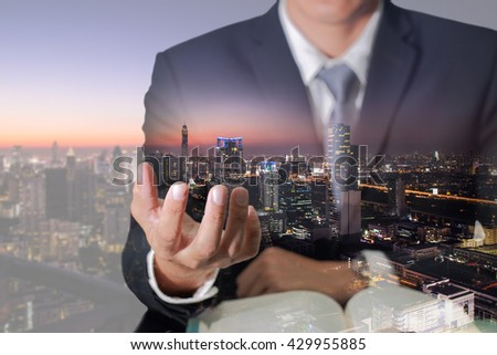 Double exposure of businessman hand hold and night cityscape as everything in hand concept. #429955885