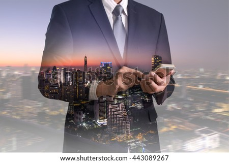 Double exposure of businessman hand hold and touch screen smart phone, mobile and night cityscape as telecommunication and technology concept. #443089267