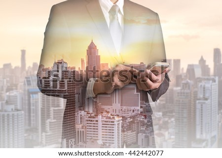 Double exposure of businessman hand hold and touch screen smart phone, mobile, cityscape and sunset as telecommunication and technology concept. #442442077