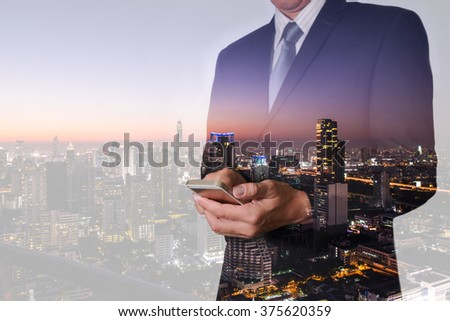 Double exposure of businessman hand hold and touch screen smart phone, mobile, street and night city as communication concept. #375620359