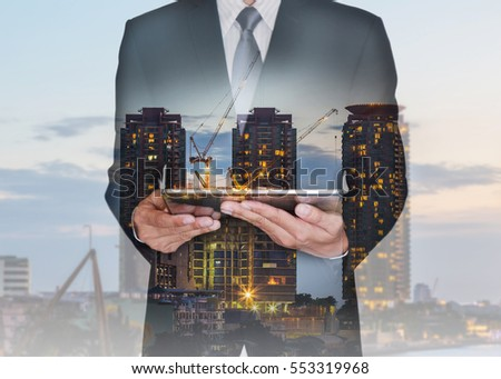 Double exposure of businessman hand hold tablet, construction crane and building in the evening, twilight as business, technology, communication and industrial concept. #553319968
