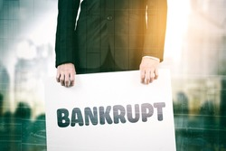 Double exposure of businessman hands holding bankrupt word on a board while standing with with cityscape background