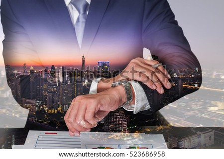 Double exposure of businessman look the watch, cityscape, urban and street in the night or twilight as appointment and business concept. #523686958