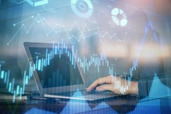 Double exposure of businessman's hands with laptop and stock market graph background. Concept of research and trading.