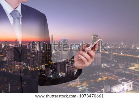 Double exposure of businessman use smartphone, communication networking telephone and cityscape urban in the night or twilight as business, technology, communication and telecom concept #1073470661